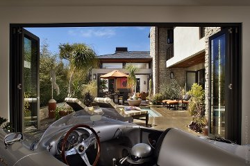 Garage door repurposed into a man cave with aluminum bi-folding door. By Lanai Doors™