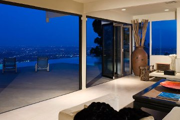 Bi-fold accordian movable glass wall modern design open to infinity pool and city skyline view from patio.