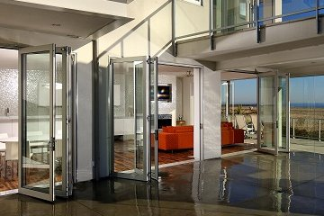 Concrete patio with sleak modern aluminum accordian door creates an open and airy atmosphere between house and patio.