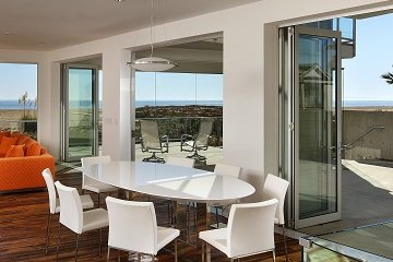 open floor concept dining room created with contemporary Aluminum folding glass wall doors double floor space.