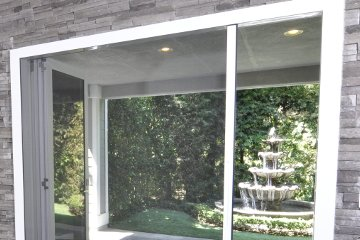 Large Screen Door with gray rock walls inside. Opening to small backyard patio bringing the outside in.