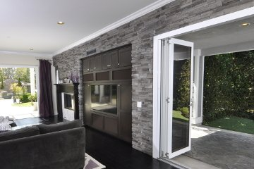 Open Concept floor plan living room glass walls with bi-fold aluminum doors leading to outdoor garden.