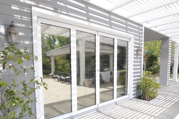 Pergola patio with gray painted house and white aluminum lanai doors. Low E glass.