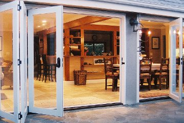 Weather tight folding patio accordian door made with Aluminum Wood Clad. Stone paver patio.