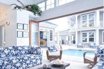 Seaside decoration idea for indoor and outdoor pool house wicker chairs with blue print couch.