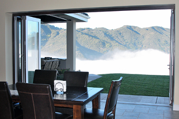 Mountain side view with Aluminum wood clad bifolding doors weathertight, insulated system. Rustic, cozy, homey design.