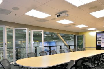 movable glasswall in conference room. with a large conference table and room divider.