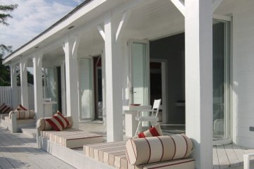 Resort Patio with lounge couches with red striped pillows. Neutral Patio breeze way with white wood deck.