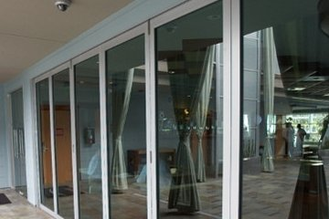Resort hotel patio with movable glass wall Aluminum bifolding glass doors. Reception patio and lounge divider.