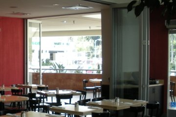 Restaurant room divider with operable glasswall accordian bi-folding doors creates flexible room design. Egress Door.