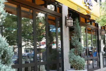 Inviting Restaurant sidewalk store front with movable glass walls made with energy efficient accordian doors.
