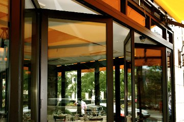 Open air patio with folding glass doors inviting outside in. ADA Compliant.