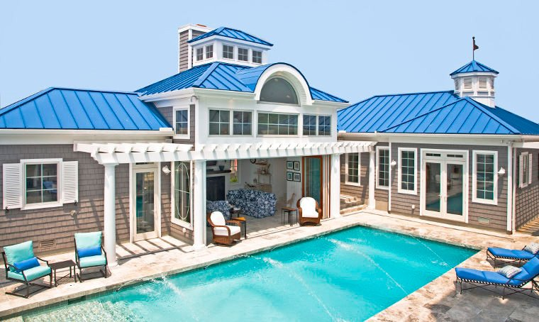 Lanai Doors Clad Folding Glass Doors connect beautiful blue Ocean City Maryland Award-winning home's living space to large pool